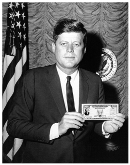President John F. Kennedy holds a U.S. Savings Bond